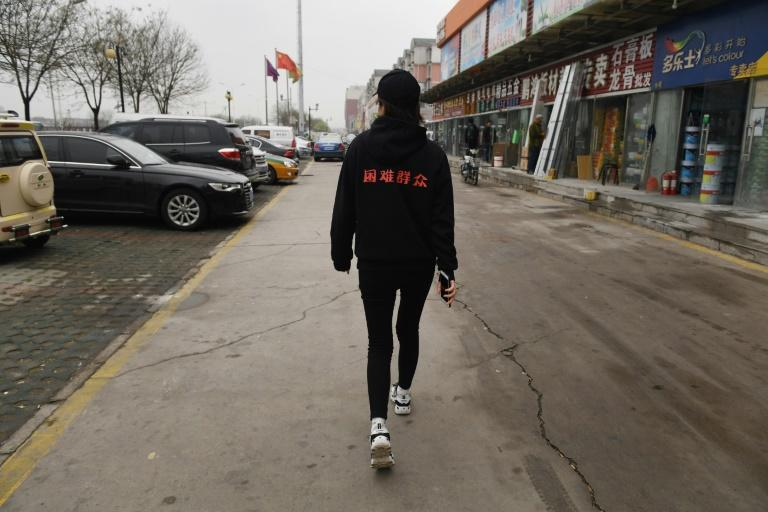 Li Wenzu, wearing a jacket reading 'The struggle of the masses', is marching from Beijing to Tianjin to demand answers about the fate of her husband