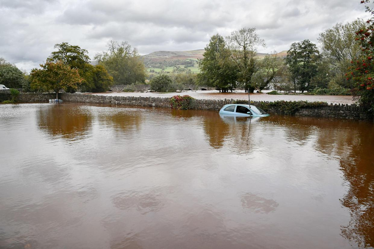 <em>A stranded vehicle sits in flood water in a car park next to the A4077 at Crickhowell, Wales (Picture: PA)</em>