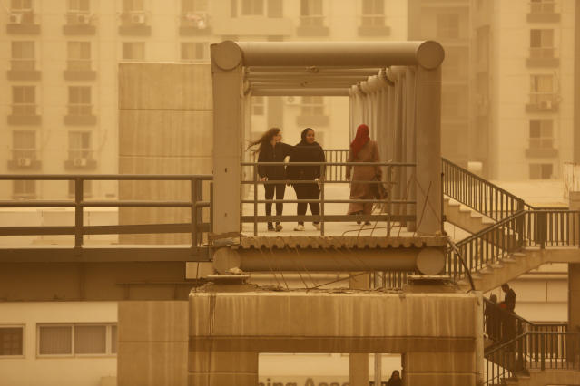 Pedestrians cross a bridge during a sandstorm in Cairo, Egypt, Wednesday, Jan. 16, 2019 as a thick sandstorm cloaked parts of the Middle East. A harsh weather front brought sandstorms, hail and rain to parts of the Middle East, with visibility down in the Egyptian capital as an orange cloud of dust blocked out the sky. (AP Photo/Amr Nabil)