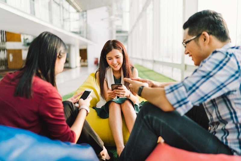 Three smiling people sitting on beanbags looking at their smartphones.
