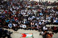 Mourners pray before the body of Palestinian man Yakoub in the Israeli-occupied West Bank