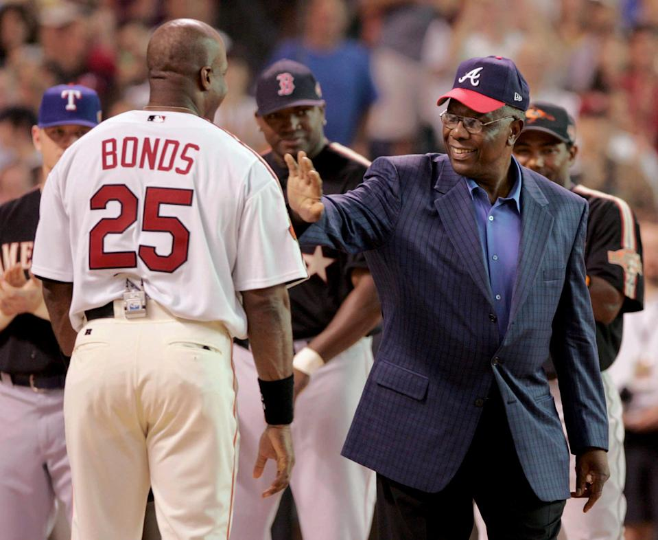 FILE- In this July 12, 2004, file photo, home run record holder Hank Aaron greets San Francisco Giants slugger Barry Bonds before the start of the All-Star Home Run Derby in Houston. Hank Aaron, who endured racist threats with stoic dignity during his pursuit of Babe Ruth's home run record and gracefully left his mark as one of baseball's greatest all-around players, died Friday. He was 86. The Atlanta Braves, Aaron's longtime team, said he died peacefully in his sleep. No cause was given.(AP Photo/Eric Gay, File)
