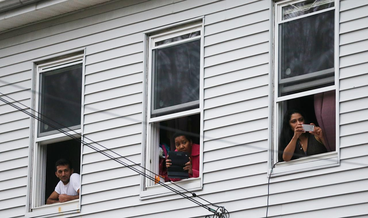 WATERTOWN, MA - APRIL 19:  Onlookers take pictures as they watch from windows while SWAT team members search for one remaining suspect at a neighboring apartment building on April 19, 2013 in Watertown, Massachusetts. Earlier, a Massachusetts Institute of Technology campus police officer was shot and killed at the school's campus in Cambridge. A short time later, police reported exchanging gunfire with alleged carjackers in Watertown, a city near Cambridge. According to reports, one suspect has been killed during a car chase and the police are seeking another - believed to be the same person (known as Suspect Two) wanted in connection with the deadly bombing at the Boston Marathon earlier this week. Police have confirmed that the dead assailant is Suspect One from the recently released marathon bombing photographs. (Photo by Mario Tama/Getty Images)