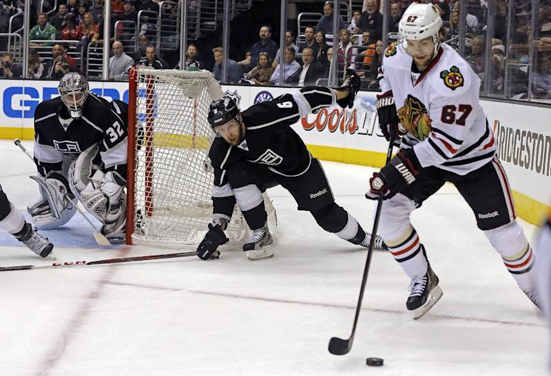 Chicago Blackhawks center Michael Frolik (67), of the Czech Republic, moves the puck as Los Angeles Kings defenseman Jake Muzzin (6) and goalie Jonathan Quick (32) watch during the first period of Game 4 of the NHL hockey Stanley Cup playoffs Western Conference finals in Los Angeles on Thursday, June 6, 2013. (AP Photo/Reed Saxon)