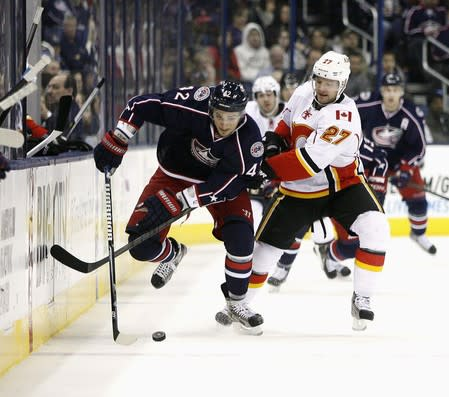 Columbus Blue Jackets Artem Anisimov races along the boards as Calgary Flames Derek Smith tries to slow him down during their NHL hockey game in Columbus