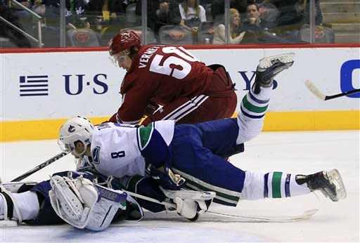 Vancouver Canucks' Chris Tanev (8) helps out goalie Cory Schneider as they both stop the puck shot by Phoenix Coyotes' Antoine Vermette during the second period in an NHL hockey game, Tuesday, Feb. 28, 2012, in Glendale, Ariz. (AP Photo/Ross D. Franklin)