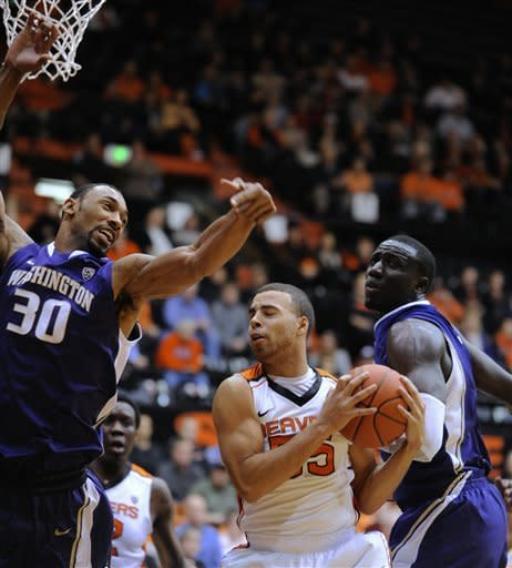 Washington's Desmond Simmons (30) battles for a rebound against Oregon State's Roberto Nelson (55) during the first half of an NCAA college basketball game in Corvallis, Ore., Wednesday Jan. 23, 2013. (AP Photo/Greg Wahl-Stephens)