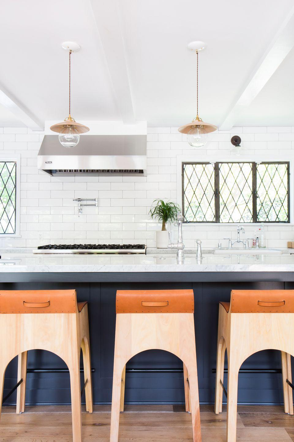 <p>Your counter stools should be as important as your dining chairs—you'll always be able to see them, and they can add some contrast to your kitchen. Amber Interiors added these leather-topped wooden stools for a surge of warm elegance. </p>