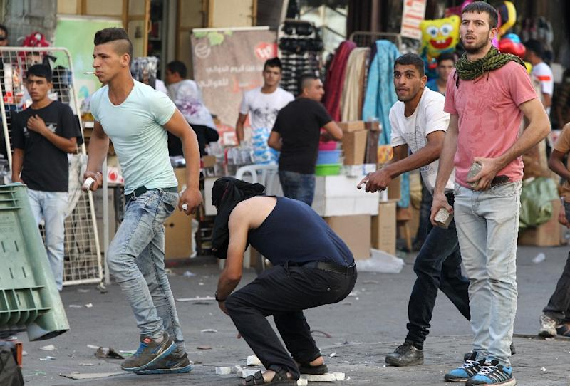 Palestinian demonstraters collect stones to throw at Israeli security forces during clashes in an area controlled by the Palestinian Authority in the centre of the West Bank city of Hebron on September 23, 2015