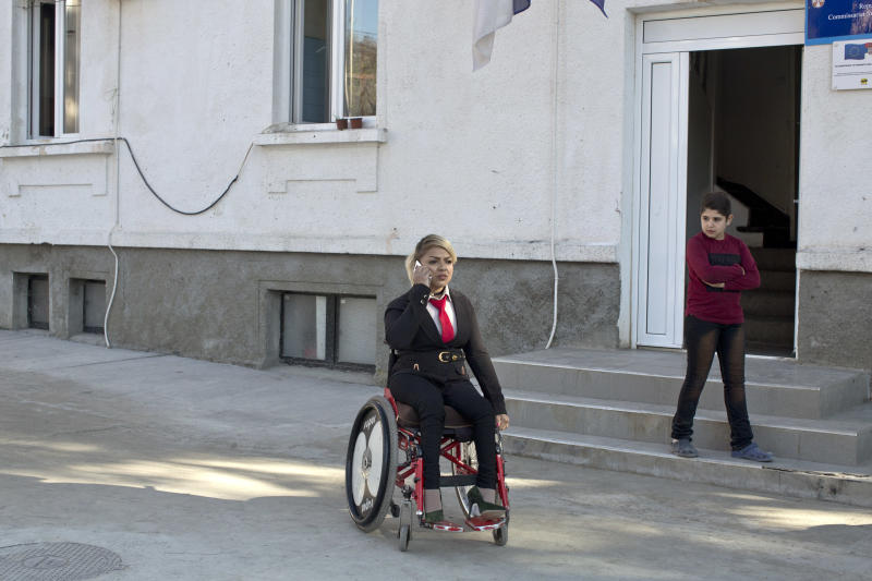 In this photo taken Tuesday, Nov. 13, 2018, Mahana Jami, 34, center, talks on the phone while inside a government run camp for refugees and migrants in Bosilegrad, some 250 kilometers southeast of Belgrade, Serbia. As a little girl in a wheelchair in Iran, Jami used to watch other children play on a slide and wondered why she couldn't do the same. She then made a promise to herself to always dream big and never let her disability stand in the way. (AP Photo/Marko Drobnjakovic)