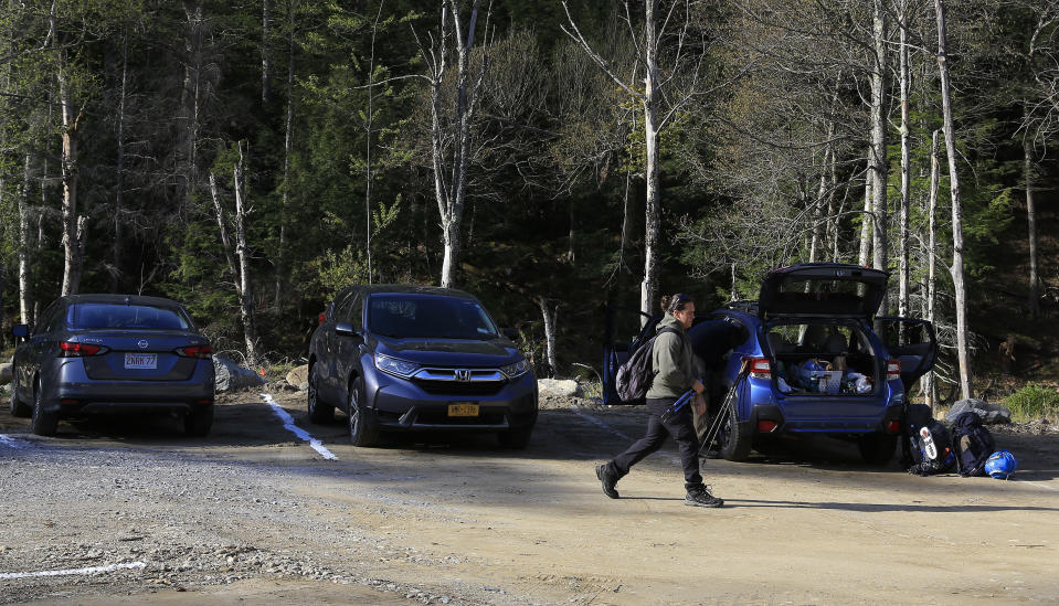 A hiker walks through the parking lot at the Adirondack Mountain Reserve trailhead, Saturday, May 15, 2021, in St. Huberts, N.Y. A free reservation system went online recently to control the growing number of visitors packing the parking lot and tramping on the trails through the private land of the Adirondack Mountain Reserve. The increasingly common requirements, in effect from Maui to Maine, offer a trade-off to visitors, sacrificing spontaneity and ease of access for benefits like guaranteed parking spots and more elbow room in the woods. (AP Photo/Julie Jacobson)