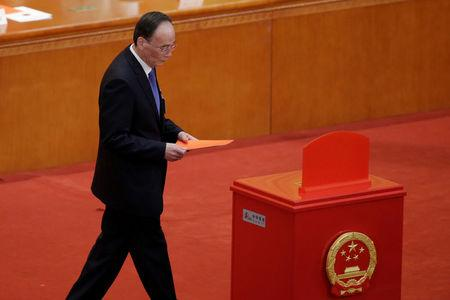 Wang Qishan, former secretary of the Central Commission for Discipline Inspection, walks with his ballot before a vote at the fifth plenary session of the National People's Congress (NPC) at the Great Hall of the People in Beijing, China March 17, 2018.  REUTERS/Jason Lee