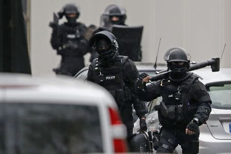 Members of French special police forces of Research and Intervention Brigade (BRI) are seen at the scene of a shooting in the street of Montrouge near Paris January 8, 2015. A policewoman was killed in a shootout in southern Paris on Thursday, triggering searches in the area as the manhunt widened for two brothers suspected of killing 12 people at a satirical magazine in an apparent Islamist militant strike. REUTERS/Charles Platiau