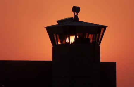 FILE PHOTO: The sun sets behind one of the guard towers at the Federal Penitentiary in Terre Haute, Indiana, June 10, 2001. REUTERS/Andy Clark/File Photo