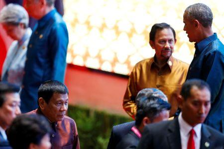 Philippine President Rodrigo Duterte arrives at the ASEAN Summit family photo while U.S. President Barack Obama chats with the Sultan of Brunei Hassanal Bolkiah in Vientiane