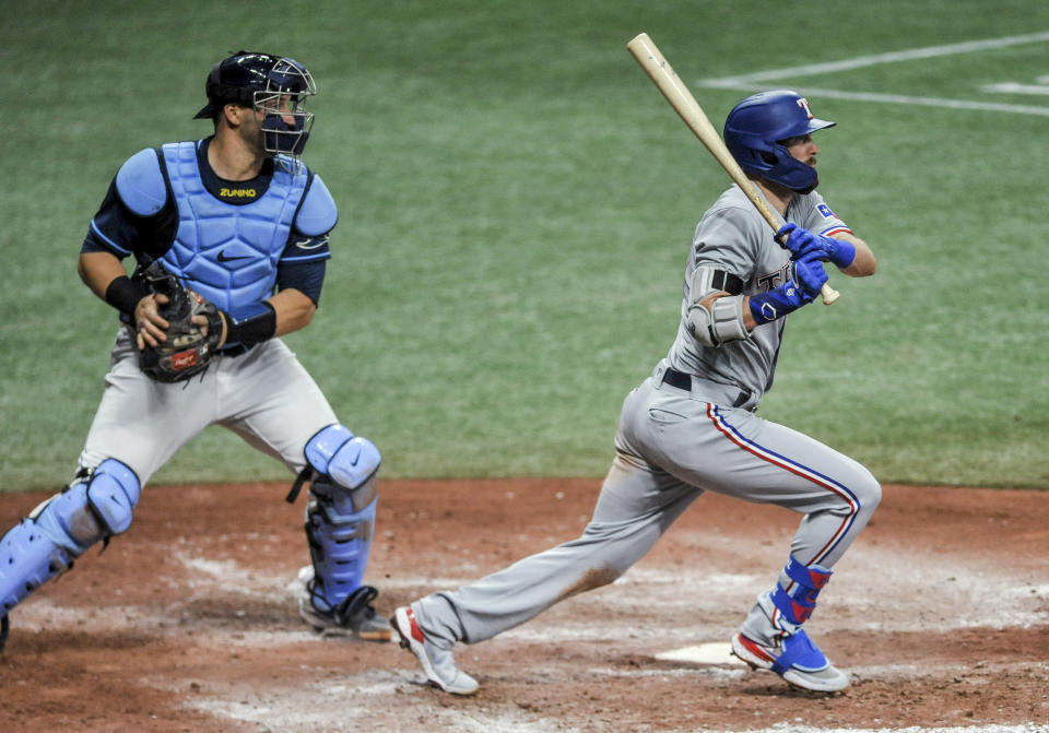Texas Rangers' David Dahl watches his two-run double next to Tamp Bay Rays catcher Mike Zunino during the seventh inning of a baseball game Wednesday, April 14, 2021, in St. Petersburg, Fla. (AP Photo/Steve Nesius)