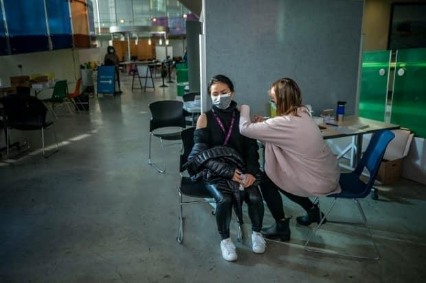 A nurse administers a Pfizer COVID-19 vaccination in Vancouver on March 4. B.C. says it expects every adult to receive a first vaccine dose by July.
