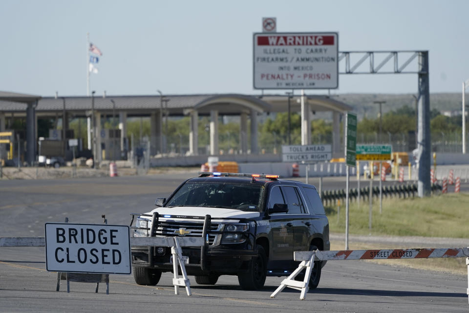 """A Texas Department of Public Safety vehicle stands at a road block near the Del Rio International Bridge, which remains closed due to a migrant encampment alongside the bridge, Friday, Sept. 24, 2021, in Del Rio, Texas. The """"amistad,"""" or friendship, that Del Rio, Texas, and Ciudad Acuña, Mexico, celebrate with a festival each year has been important in helping them deal with the challenges from a migrant camp that shut down the border bridge between the two communities for more than a week. Federal officials announced the border crossing would reopen to passenger traffic late Saturday afternoon and to cargo traffic on Monday. (AP Photo/Julio Cortez)"""