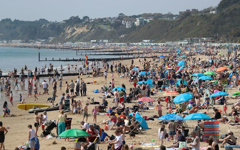 People enjoy the hot weather at Bournemouth beach, Dorset, as Britain is set for a sunny Easter  - PA