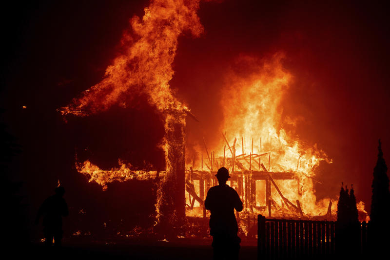FILE - In this Nov. 8, 2018 file photo, a home burns as a wildfire called the Camp Fire rages through Paradise, Calif. Experts say it's hard to know what might have happened had the power stayed on, or if the utility's proactive shutoffs are to thank for California's mild fire season this year. (AP Photo/Noah Berger, File)