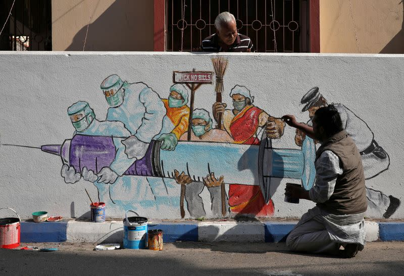 Man applies finishing touches to graffiti representing a vaccine in Kolkata