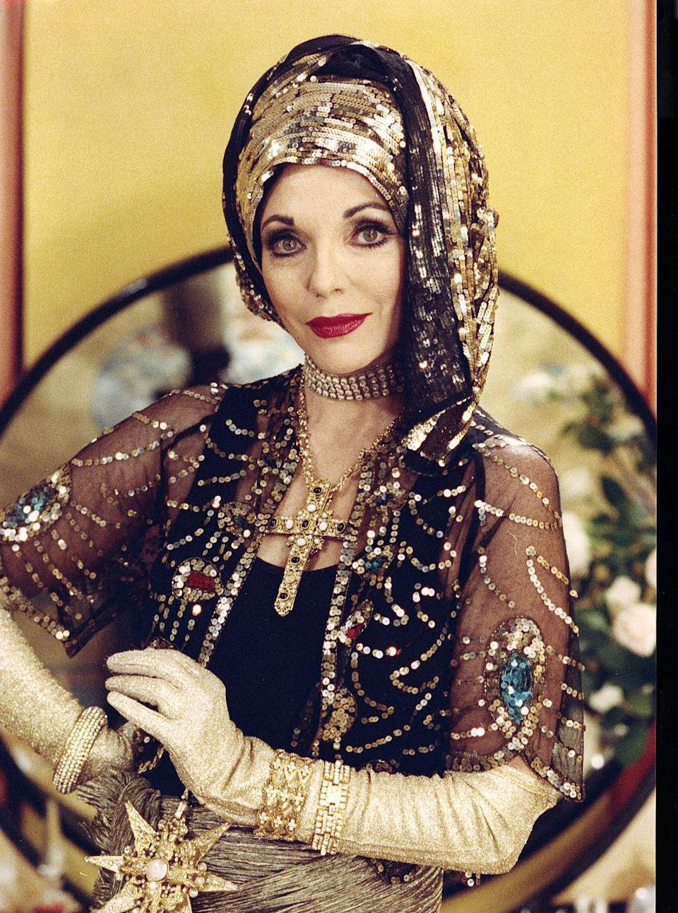 """<p>Collins once called herself a """"fiend for costume jewellery"""", with """"countless pairs of rhinestone earrings"""", so she was aptly attired in layers of diamante jewels and sequins for her role as a wealthy socialite in the film Decadence. </p>"""