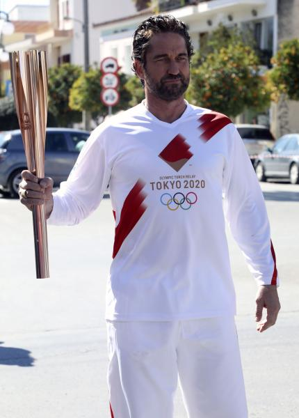 """US actor Gerard Butler poses as a torchbearer during the Olympic torch relay of the 2020 Tokyo Olympic Games in the southern Greek town of Sparta, Friday, March 13, 2020. Greece's Olympic committee says it is suspending the rest of its torch relay for the Olympic flame due to the """"unexpectedly large crowd"""" that gathered to watch despite repeated requests for the public to stay away to prevent the spread of the new coronavirus. (AP Photo)"""