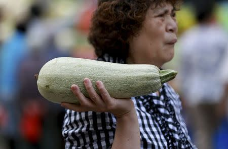 A woman holds a summer squash as she walks at a morning market in Shenyang