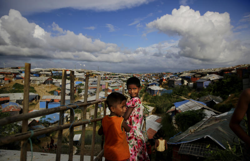 Rohingya children stand next to a bamboo fence overlooking an expanse of makeshift bamboo and tarp shelters at Kutupalong refugee camp, where they have been living amid uncertainty over their future after they fled Myanmar to escape violence a year ago, in Bangladesh, Sunday, Aug. 26, 2018. (AP Photo/Altaf Qadri)