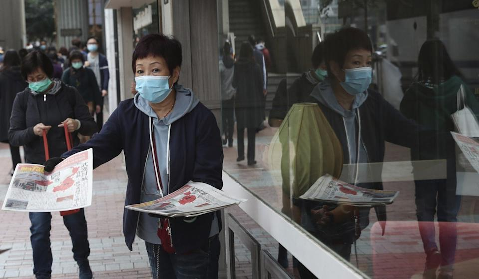 A woman wearing a protective face mask delivers a leaflet on the Wuhan coronavirus in Wuhan in Hong Kong on January 24. Photo: AP