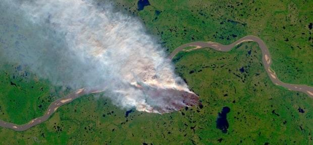 A wildfire seen from the air near Tsiigehtchic in 2019. Climate change is making typical cycles of burn and soak in N.W.T. forests less predictable, and weather events more extreme.