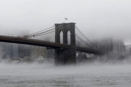 FILE PHOTO - The Brooklyn Bridge is seen partially in fog from in front of the Manhattan skyline in Brooklyn, New York, U.S., January 12, 2018. REUTERS/Shannon Stapleton