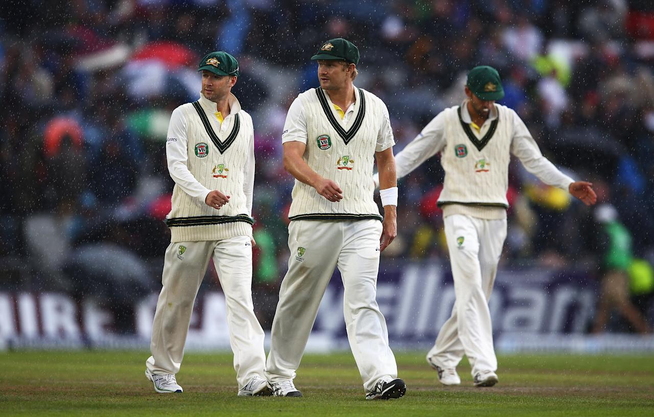 MANCHESTER, ENGLAND - AUGUST 05: (L-R) Michael Clarke, Shane Watson and Nathan Lyon of Australia walk off as rain falls during day five of the 3rd Investec Ashes Test match between England and Australia at Emirates Old Trafford Cricket Ground on August 5, 2013 in Manchester, England. (Photo by Michael Steele/Getty Images)
