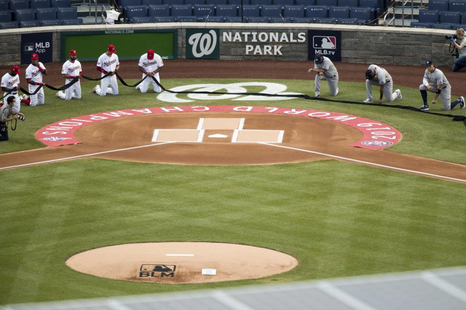 The New York Yankees and the Washington Nationals put down a black ribbon and take a knee to honor Black Lives Matter before playing an opening day baseball game at Nationals Park, Thursday, July 23, 2020, in Washington. (AP Photo/Andrew Harnik)