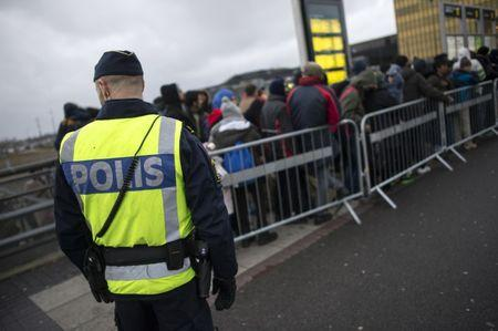 A police officer keeps guard as migrants arrive at Hyllie station outside Malmo