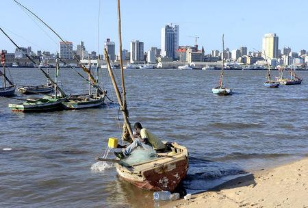 FILE PHOTO: A fisherman cleans his boat beneath Maputo's skyline