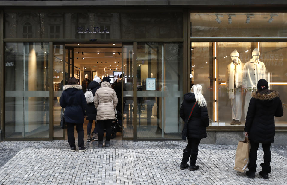 People enter a store in Prague, Czech Republic, Thursday, Dec. 3, 2020. A sign of normalcy has returned to the Czech Republic ahead of the Christmas period after the government eased some of its most restrictive measures imposed to contain the recent massive surge of coronavirus infections. On Thursday all stores, shopping malls, restaurants, bars and hotels were allowed to reopen. (AP Photo/Petr David Josek)