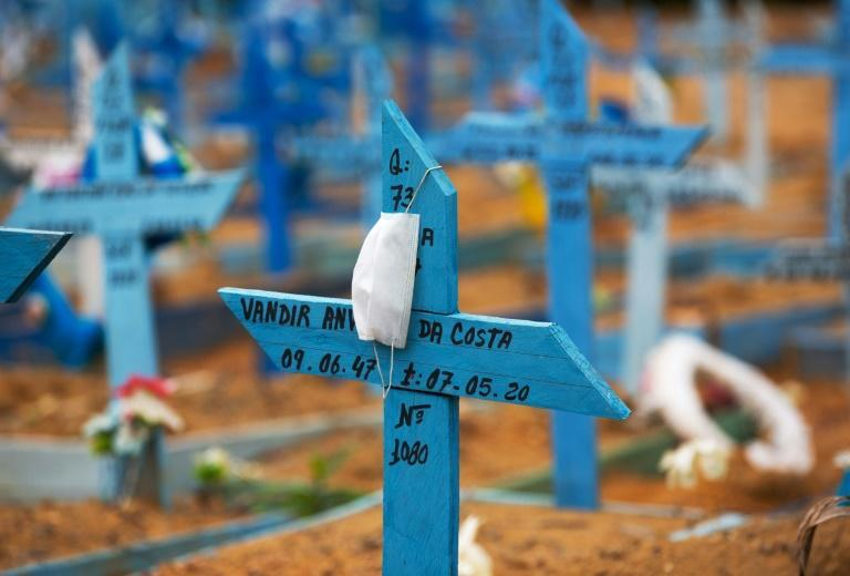 A face mask rests on a cross in an area reserved for the burial of COVID-19 victims at the Nossa Senhora Aparecida cemetery in Manaus, Brazil