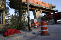 A homeless man sleeps next to construction for the new Signature Bridge, Thursday, April 8, 2021, in the Overtown neighborhood of Miami. At right is the original Interstate 395 bridge built in the 1960's which forced out thousands of residents. (AP Photo/Lynne Sladky)