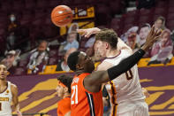 Minnesota's Liam Robbins (0) passes the ball as Illinois' Kofi Cockburn (21) defends in the first half of an NCAA college basketball game, Saturday, Feb. 20, 2021, in Minneapolis. (AP Photo/Jim Mone)