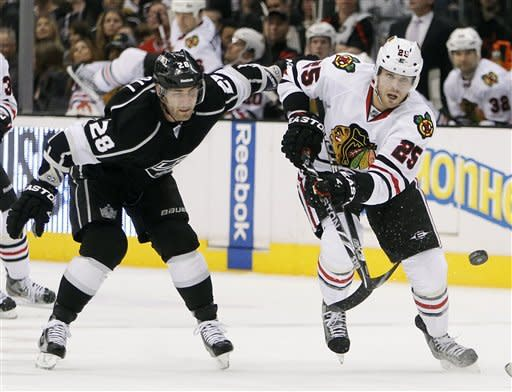 Chicago Blackhawks left wing Viktor Stalberg (25), of Sweden, sends the puck upice with Los Angeles Kings center Jarret Stoll (28) defending during the first period of an NHL hockey game in Los Angeles, Saturday, Feb. 25, 2012. (AP Photo/Alex Gallardo)