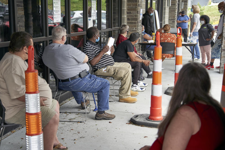 Job seekers exercise social distancing as they wait in line, seated in spaced-apart chairs, outside the entrance of a building.