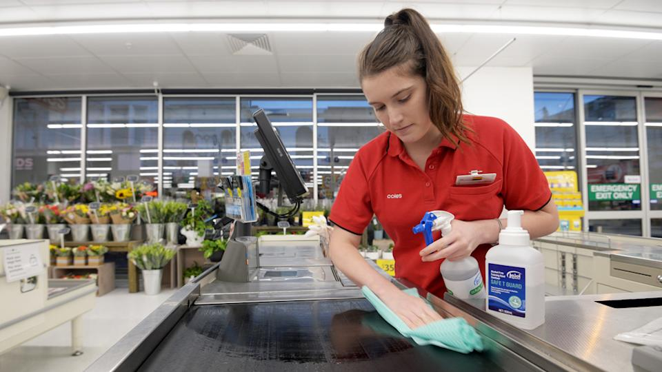 A Coles worker cleaning the checkout with sanitiser.