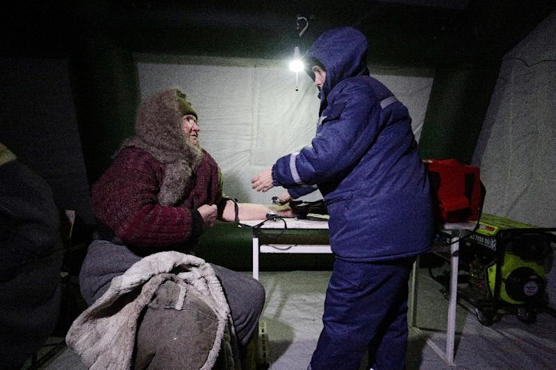 A doctor helps an elderly woman in Avdiivka after the town's power was cut (AFP Photo/Aleksey FILIPPOV)