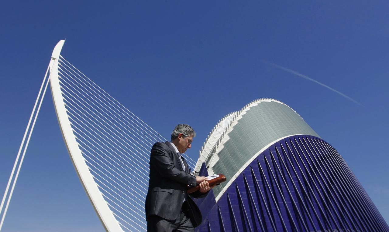 A pedestrian walks past the Agora building and the Azud D'or bridge at the City of Arts and Sciences, designed by architect Santiago Calatrava, in Valencia April 25, 2012. The cost of both structures escalated up to 150 million euros, according local media. REUTERS/Heino Kalis (SPAIN - Tags: SOCIETY BUSINESS)