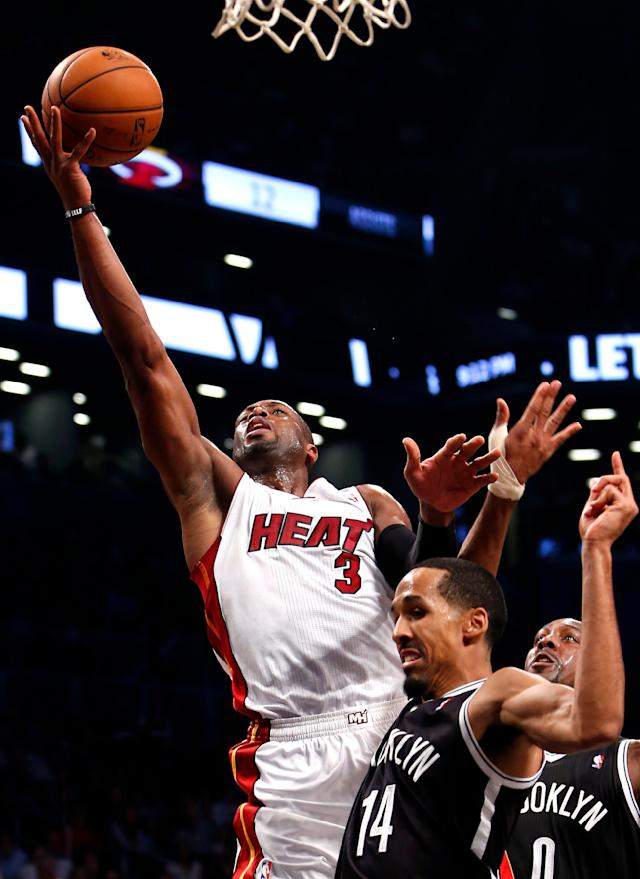 Miami Heat's Dwayne Wade (3) is fouled on his way to the basket by Brooklyn Nets' Shaun Livingston (14) during an NBA basketball game Friday, Nov. 1, 2013, in New York. (AP Photo/Jason DeCrow)