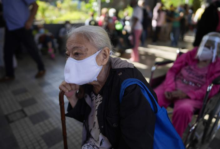 A elderly woman waits outside of a vaccination center looking to be inoculated with a second dose of the Sputnik V COVID-19 vaccine, in Caracas, Venezuela, Thursday, Sept. 16, 2021. The Venezuelan government is beginning rollouts of second doses following months of delays. (AP Photo/Ariana Cubillos)