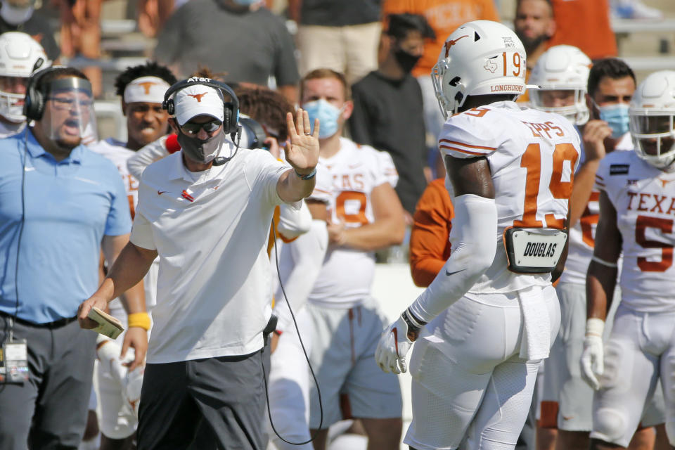 Texas head coach Tom Herman gives instructions to Texas tight end Malcolm Epps (19) during overtime of an NCAA college football game in Dallas, Saturday, Oct. 10, 2020. Oklahoma defeated Texas 53-45 in overtime.(AP Photo/Michael Ainsworth)
