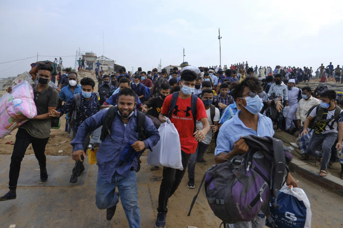 Thousands of people leaving for their native places to celebrate Eid-al-Fitr rush to the Mawa ferry terminal ignoring risks of coronavirus infection in Munshiganj, Bangladesh, Thursday, May 13, 2021. (AP Photo/Mahmud Hossain Opu)