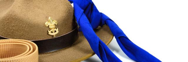 brown brim hat (hat of scout) isolated on white while blue neck time and beige belt